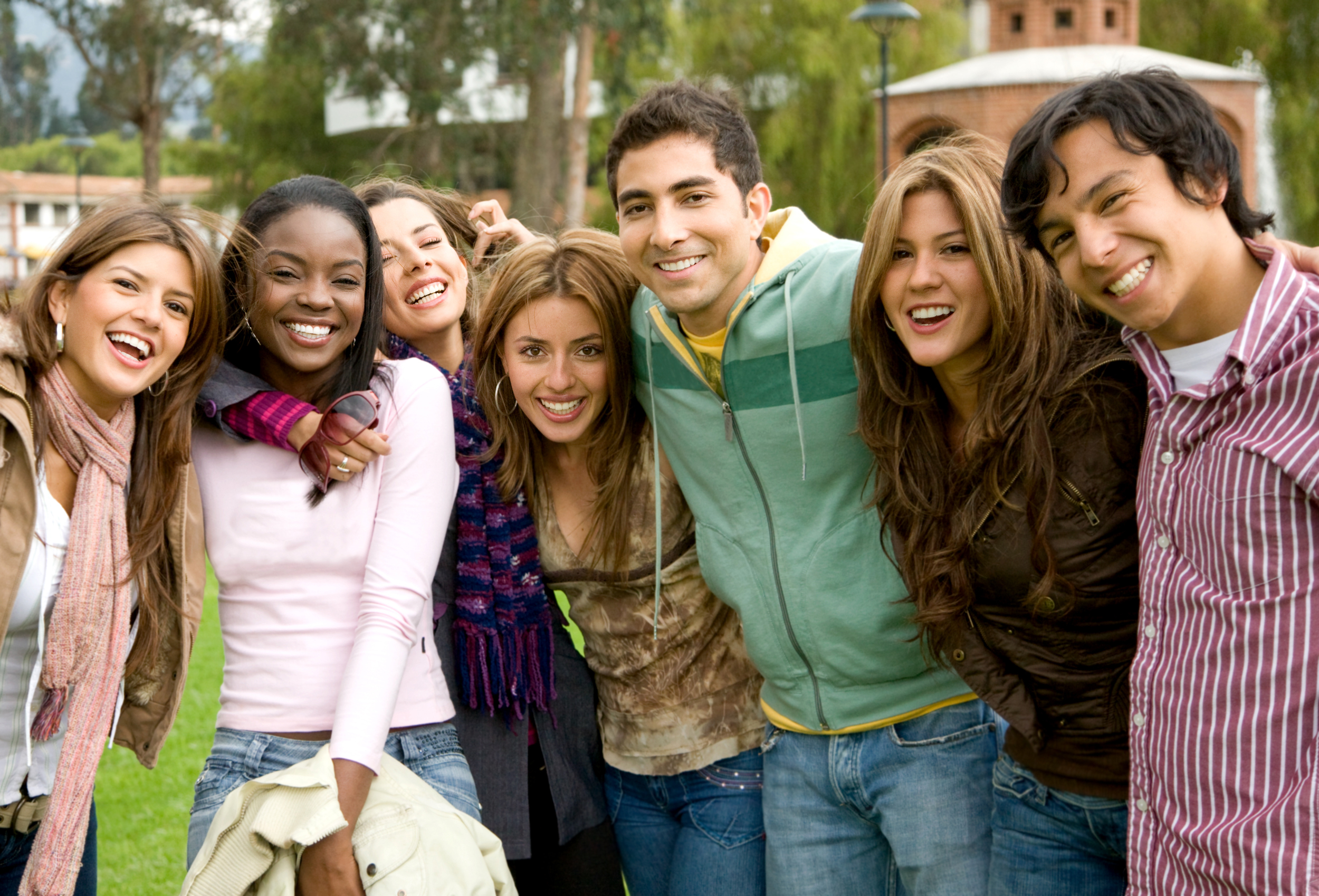 Group of college aged students gathered together with arms around one another