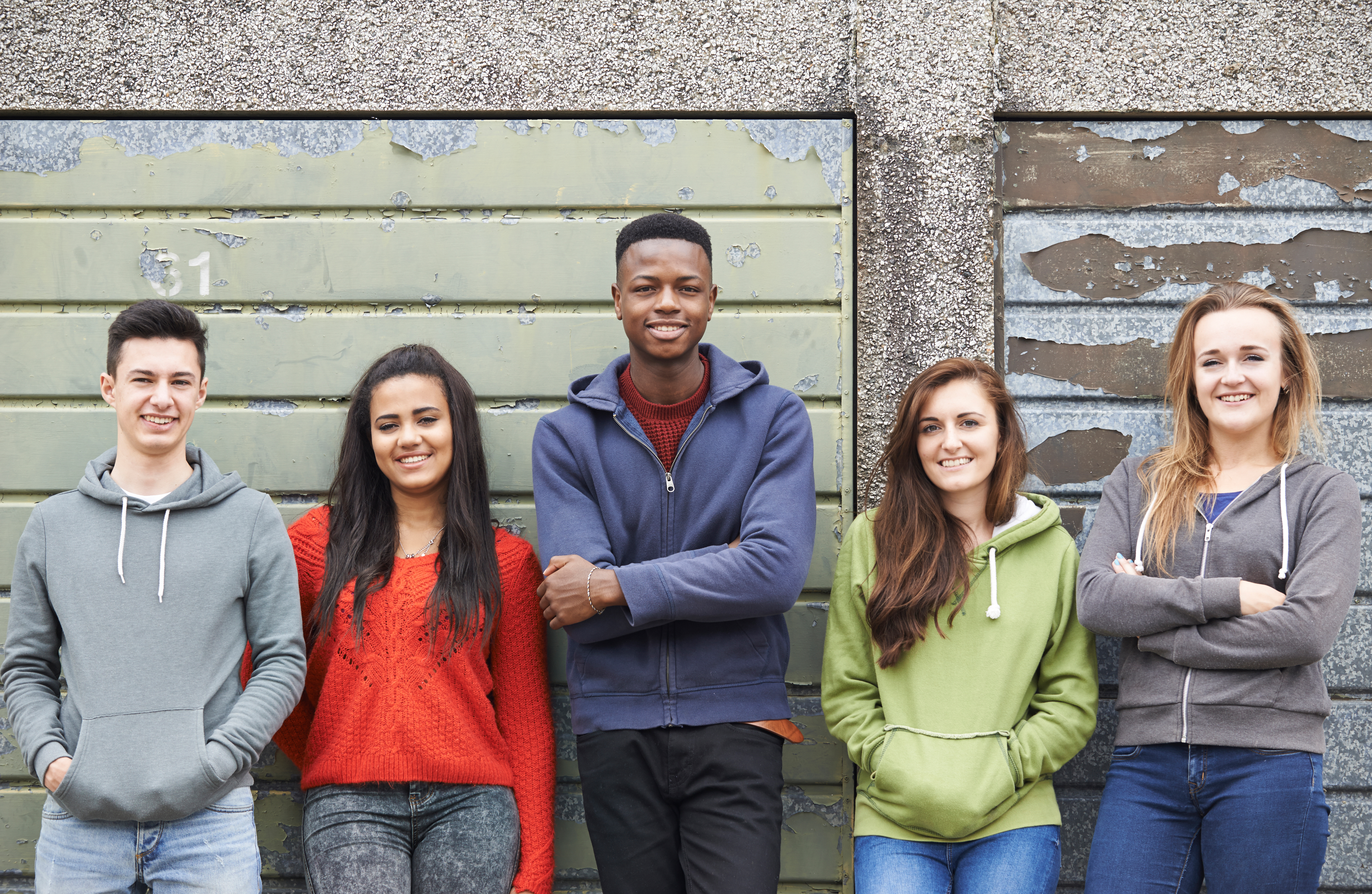 Group of teens standing next to each other against a wall